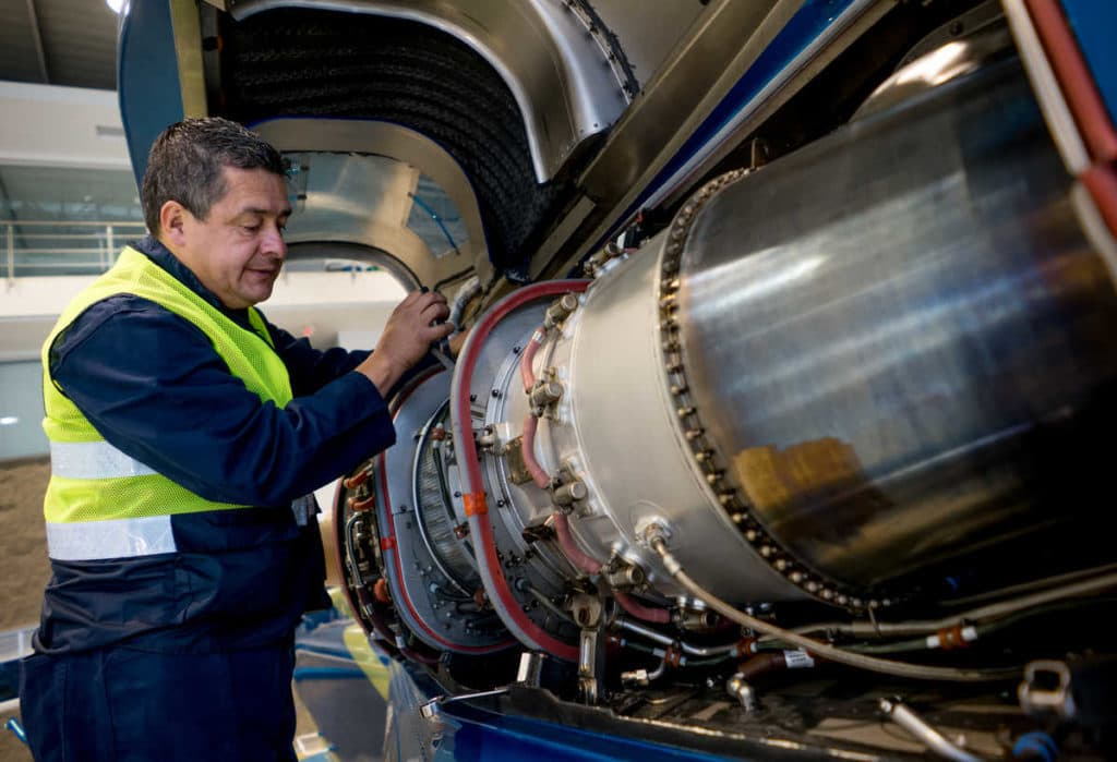 Portrait of a Latin American mechanic fixing the engine on an airplane - people at work concepts